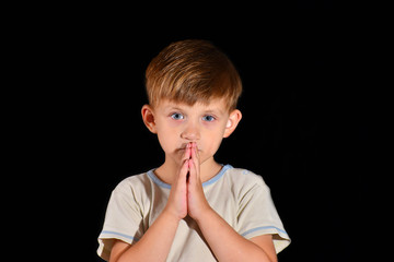A little boy prays to God with his hands tucked open with his eyes open.