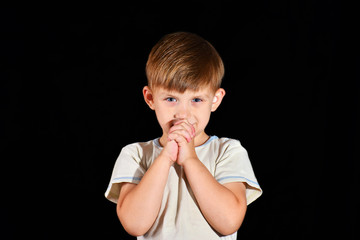 The little boy prays to God with his arms folded, his eyes open, and with a grin on his face