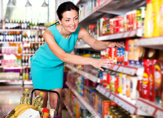 Woman choosing jar of tomato paste