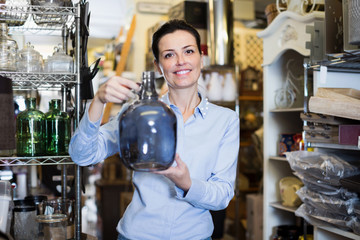 Portrait of smiling woman choosing glass item at store