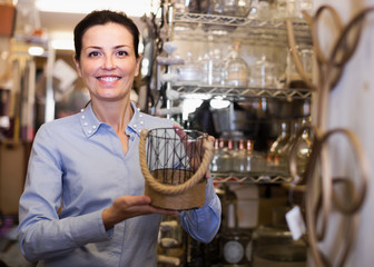 Portrait of smiling female holding  glass item in store