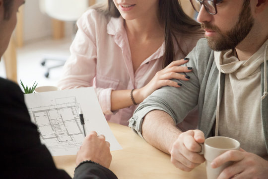 Close up of millennial couple visiting architect or designer office, consulting about future house project, young spouses deciding to buy first apartment or flat together or planning home renovation.