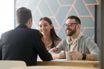 Happy millennial couple exited to buy first house together, consulting about apartment purchase in broker or realtor office, spouses smiling receiving good offer from real estate agent.