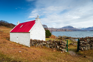 Wall Mural - A pretty cottage with a red roof on the shores of Loch Shieldaig in Scotland and on the NC500 coastal tourist route