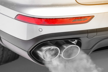 Close up of double chrome exhaust pipe of a white powerful modern sport car.