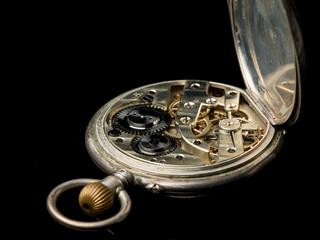 Old pocket watch on a black reflective surface