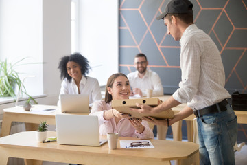 Male deliveryman giving pizza cardboard box to smiling female employee ordering takeout food for lunch break in office, courier bringing takeaway meal to excited colleagues having shared dinnertime