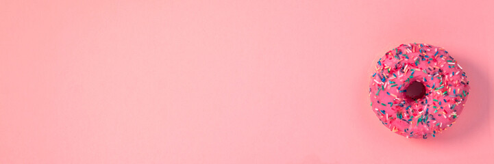 Panoramic view on pink donut with colorful sprinkles on an empty pink pastel background