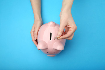 Female hand putting coin into piggy bank on blue background Wall mural