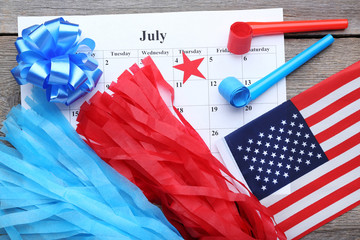 American flag, blower and paper July calendar on wooden table