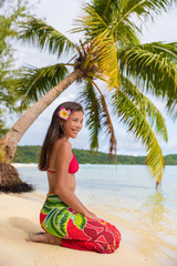 Beach woman relaxing on Bora Bora Tahiti island under the sun wearing polynesian skirt and monoi flower with palm tree background. Polynesia culture travel concept.