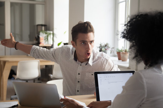Mad male worker yelling at female colleague asking her to leave office, multiracial coworkers disputing during business negotiations, employees cannot reach agreement, blaming for mistake or crisis
