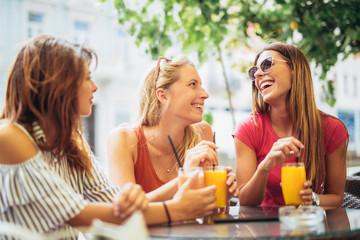 Three beautiful friends in a cafe having fun