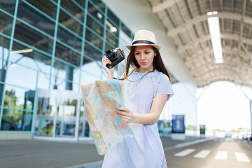 Young concerned traveler tourist woman in hat hold retro vintage photo camera, looking at paper map at international airport. Female passenger traveling abroad on weekends getaway. Air flight concept.