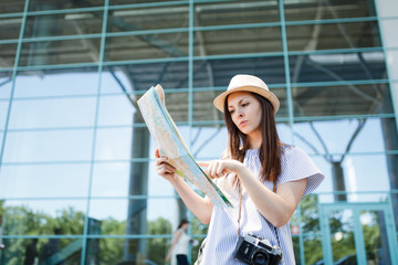 Young traveler tourist woman with retro vintage photo camera search route in paper map at international airport. Female passenger traveling abroad to travel on weekends getaway. Air flight concept.