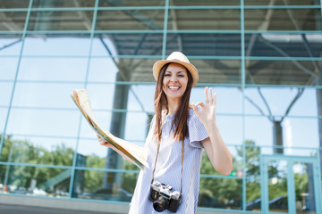 Young joyful traveler tourist woman with retro vintage photo camera hold paper map, show OK gesture at international airport. Female passenger traveling abroad on weekends getaway. Air flight concept.