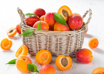 Fresh apricots on a white wooden background.