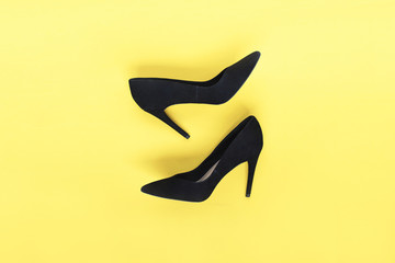 Stylish fashion black shoes high heels on yellow background. Flat lay, top view trendy background. Fashion blog look.