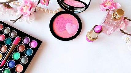 Makeup set with a pink blush, lipstick, eyeshadow multicolor palette, perfume, pearl necklace and flowers on white background