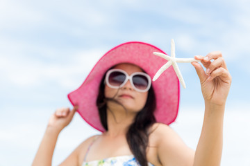 Beautiful woman wearing hat beach and sunglasses and holding starfish on hands over sandy beach, green sea and blue sky background for summer holiday and vacation concept.
