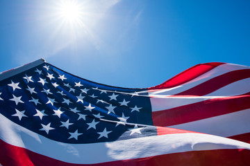 Close up United States of America flag on the blue sky background. USA Independence day, 4 July. Wall mural