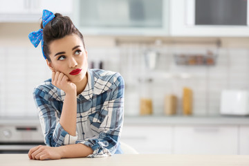 Portrait of funny young housewife in kitchen