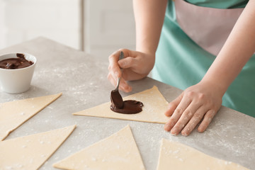Woman preparing tasty croissants with chocolate paste on table, closeup