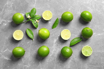 Flat lay composition with fresh ripe limes on gray background, top view