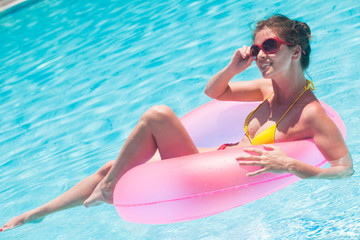 pretty woman floating with pink rubber inflatable ring in swimming pool and having fun