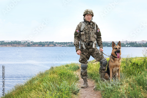 Man in military uniform with German shepherd dog near river