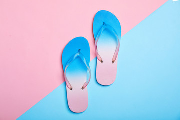 Stylish beach flip-flops on color background, top view