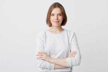 Obraz Closeup of happy pretty young woman in longsleeve standing with hands folded and looking directly in camera isolated over white wall Feeling confident - fototapety do salonu