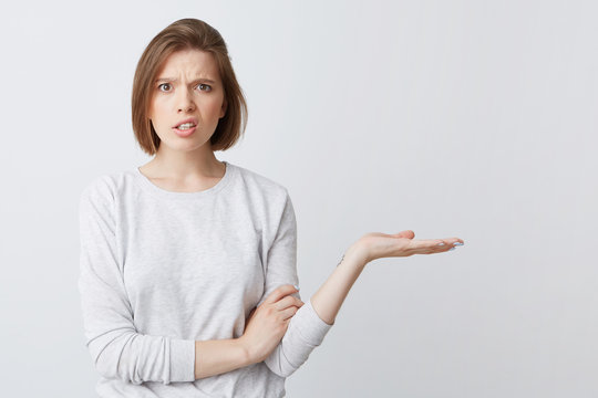 Closeup of embarrassed displeased young woman in longsleeve looks confused and holding copyspace on palm isolated over white background