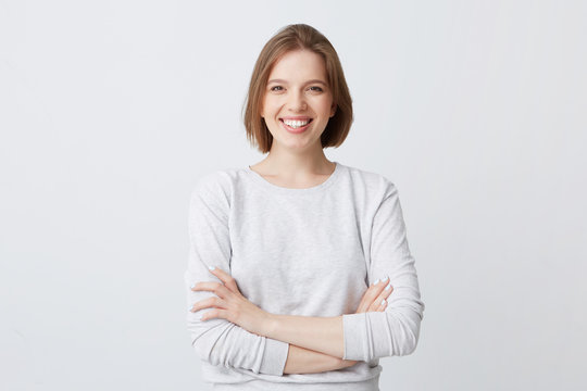 Portrait of cheerful attractive young woman in longsleeve standing with arms crossed and smiling isolated over white background Looks confident