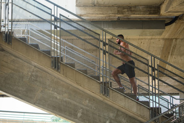 Muscular man running up the stairs by day
