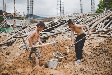 Little boys labor working in commercial building structure, World Day Against Child Labour concept.