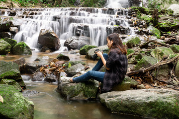 Beautiful asian woman taking a photo around mountains near the river at spring time with camera