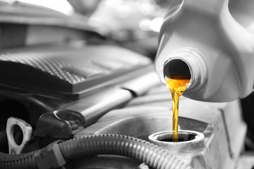 Pouring oil into car engine, closeup