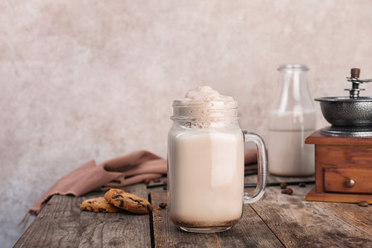Mason jar with delicious milk shake on wooden table