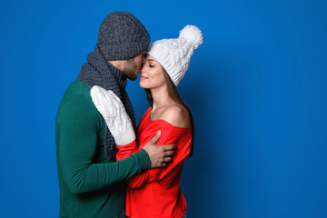 Young couple in warm clothes on color background. Christmas celebration