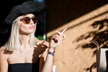 Beautyful stylish young blonde woman smoking cigarettes outdoors in han and sunglasses