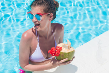 Beautiful young woman in sunglasses with coconut cocktail in hand in luxury pool
