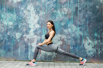 Fitness sport girl in fashion sportswear doing yoga fitness exercise in the street, outdoor sports,...