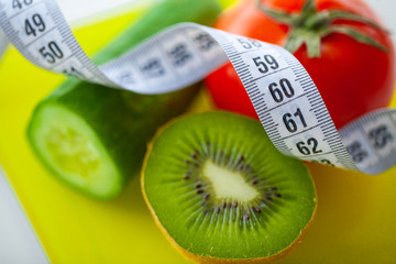 Diet or Weight Control Concept. Fruits and Vegetables With Measuring Tape On Weight Scale. Fitness and Healthy Food Diet Concept.