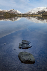 Stones in shallow water and perfect reflection of snow covered mountains and sky in the still waters of Grasmere, Lake District National Park, UNESCO World Heritage Site, Cumbria, England, United Kingdom, Europe