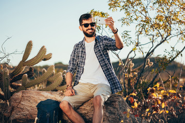 Man with backpack taking selfie with his mobile phone during desert hike