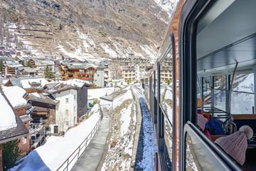 ZERMATT, SWITZERLAND - APRIL 13. 2018: Red train climbing up to Gornergrat station on Zermatt, Switzerland. The Gornergrat rack railway is the highest open-air railway in Europe.