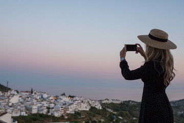 Traveler taking a picture with her smartphone in small Spanish village