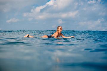 Surfer girl on the surfboard. Woman with surfboard in ocean. Surfer and ocean