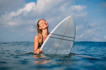 Smiled surfer woman with surfboard. Woman with surfboard in ocean.